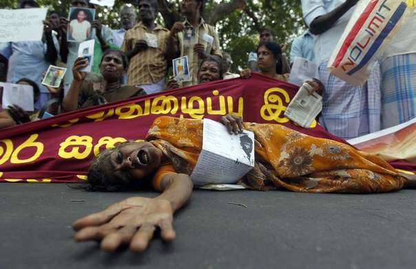 A Tamil woman cries as she holds up an image of her disappeared family member during the war against Liberation Tigers of Tamil Eelam (LTTE) at a protest in Jaffna, about 400 kilometres (250 miles) north of Colombo August 27, 2013. REUTERS/Dinuka Liyanawatte