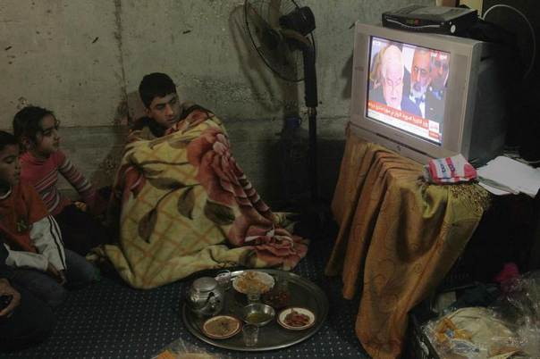 Syrian refugees watch the Geneva-2 peace conference on television at the port city of Sidon, southern Lebanon, January 22, 2014. REUTERS/Ali Hashisho