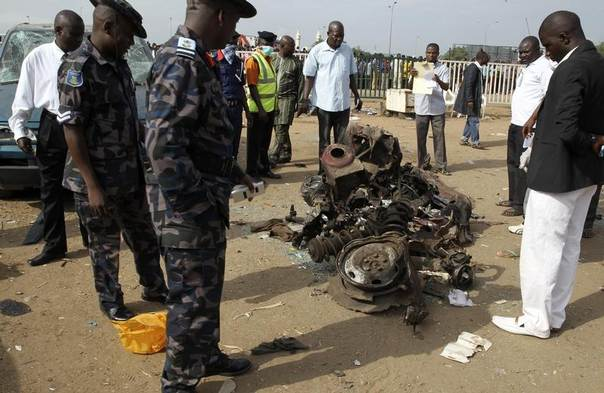 Air Commodore Charles Otegbade (3rd L), director of search and rescue operations, looks at the wreckage after a bomb blast at Nyayan bus terminal in Abuja, Nigeria, April 14, 2014. REUTERS/Afolabi Sotunde