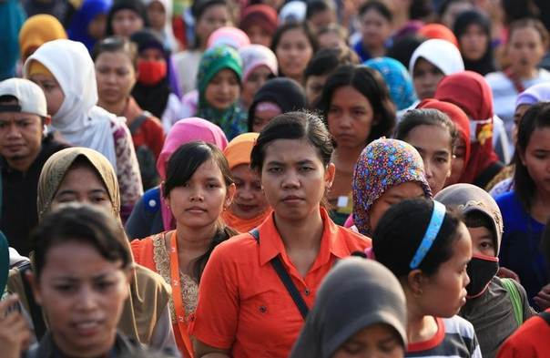 Women workers walk in front of their shoe factory as they return home in Tangerang, Indonesia's Banten province March 7, 2014.  REUTERS/Beawiharta