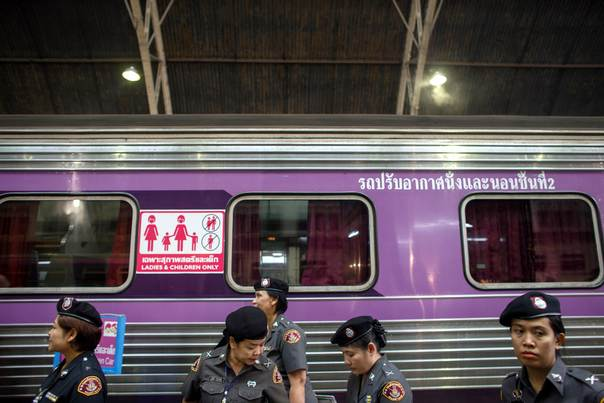 Railway police officers stand in front of a women- and children-only train carriage at Hualamphong Station in Bangkok, on August 1, 2014. Thailand's national railway began operating special women- and children-only train carriages on Friday. REUTERS/Athit Perawongmetha