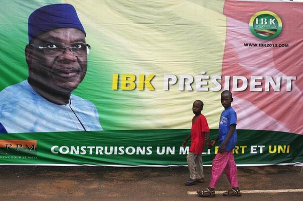 Boys walk in front of a poster of Mali's President-elect Ibrahim Boubacar Keita in Bamako August 13, 2013 REUTERS/Joe Penney