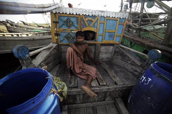 A Muslim boy rests on a boat used to escape violence in Kyukphyu, Myanmar, near a refugee camp outside of Sittwe October 30, 2012.