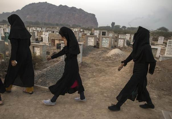 Ahmadi women walk past graves at the Ahmadi graveyard in the town of Rabwa December 9, 2013. Three years ago, 86 Ahmadis were killed in attacks in Lahore. There have been no mass attacks since then, but targeted killings are rising. REUTERS/Zohra Bensemra