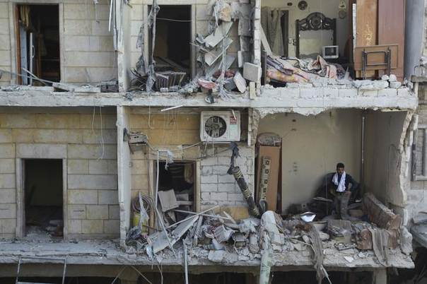 A man stands in a building damaged by what activists said were air strikes from forces loyal to Syria's President Bashar al-Assad in the Maysar neighbourhood of Aleppo December 28, 2013. REUTERS/Jalal Alhalabi
