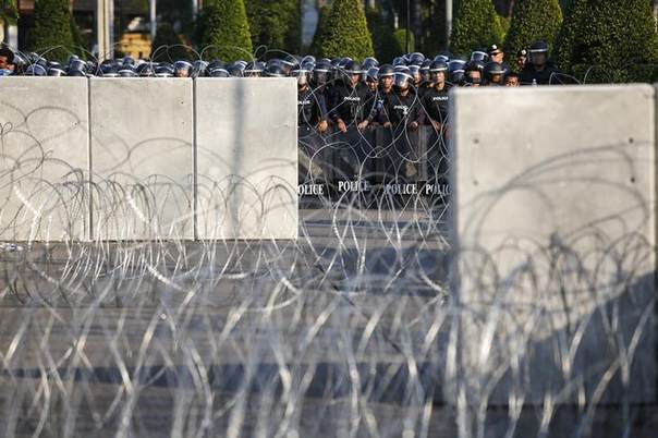 Riot police officers stand guard behind barricades as anti-government protesters rally outside the Thai Royal Police Club in Bangkok, Thailand, January 29, 2014. REUTERS/Athit Perawongmetha