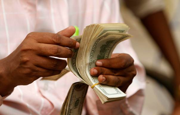 A Somali man counts his money at a Dahabshiil money transfer office in