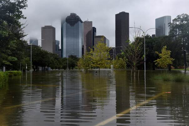 The downtown skyline is reflected in the flood water at
