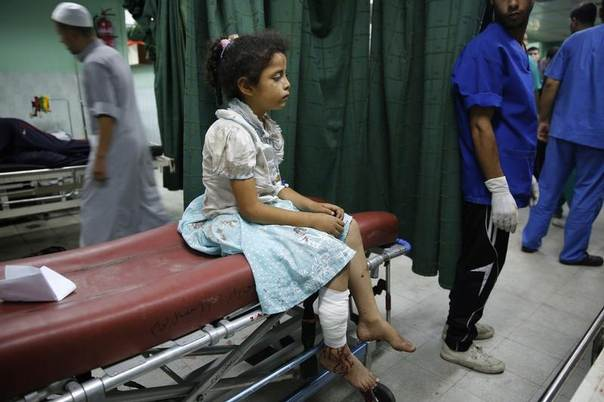 A Palestinian girl who medics said was injured by Israeli shelling during an Israeli ground offensive, sits on a bed at a hospital in Beit Lahita in the northern Gaza Strip July 30, 2014. REUTERS/Finbarr O'Reilly