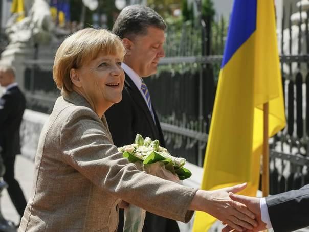 Germany's Chancellor Angela Merkel shakes hands with an unidentified official as she walks with Ukraine's President Petro Poroshenko in Kiev, Ukraine, August 23, 2014. REUTERS/Gleb Garanich
