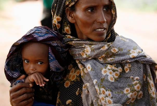 A mother brings her baby for medical checks and food distribution at a feeding center outside Mandera town, Kenya on November 15, 2007. REUTERS/Radu Sigheti