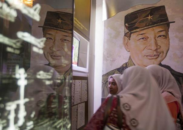 Indonesian women look at exhibits at the Suharto museum in Yogyakarta, March 29, 2014. Once dubbed the smiling general despite his iron rule of more than three decades, the image of former President Suharto now waves genially from the election campaign poster of one of his daughters. REUTERS/Dwi Oblo