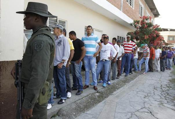 Men wait to vote in presidential elections in Corinto May 25, 2014. REUTERS/Jaime Saldarriaga