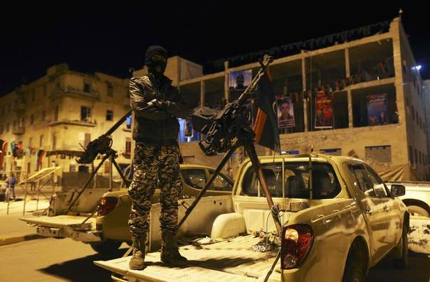 A member of a heavily armed militia group stands near his weapon in Freedom Square in Benghazi 18, February 2014. LIBYA-MILITIAS/ REUTERS/Esam Omran Al-Fetori