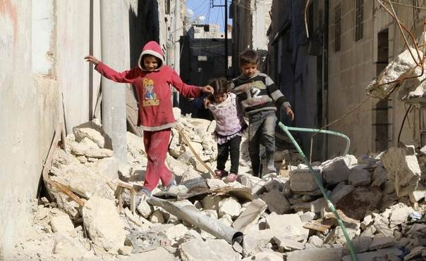 Children walk on the debris of damaged buildings in the al-Myassar neighbourhood of Aleppo March 22, 2014. REUTERS/Mahmoud Hebbo