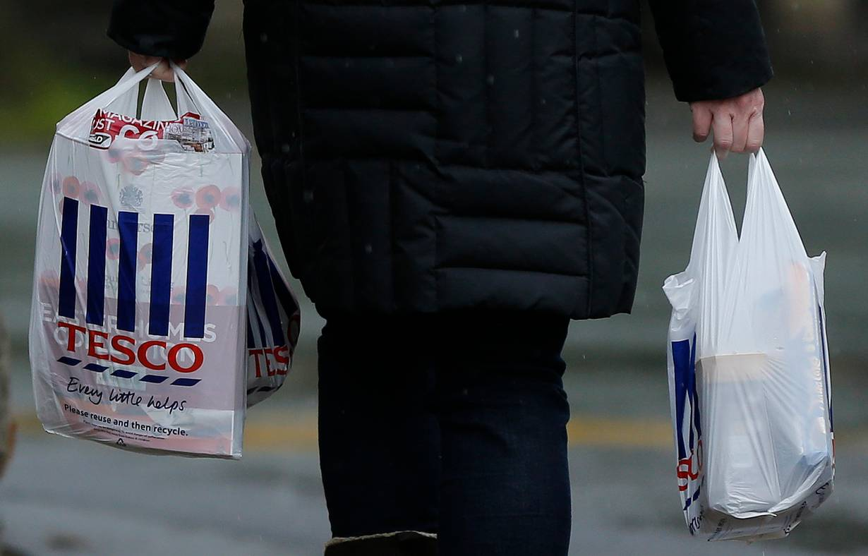 Archive Photo: A shopper carries bags as she leaves a Tesco store near Manchester, northern England April 18, 2012. REUTERS/Phil Noble