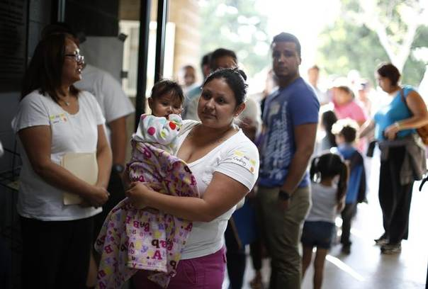 Maria Alvarado, 30, holds her 10-month-old son Kevin Rios as she waits in line at a health insurance enrolment event in Cudahy, California March 27, 2014.  REUTERS/Lucy Nicholson