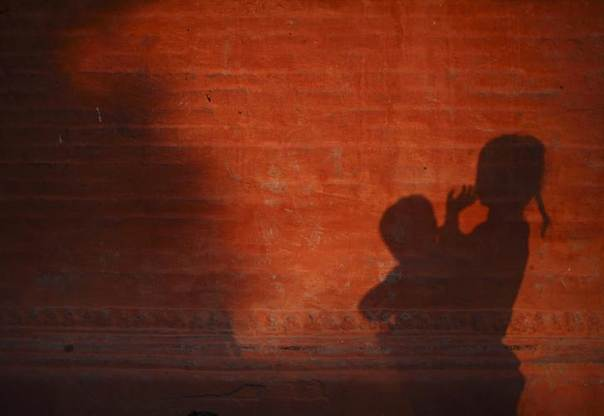 A girl carrying her younger brother casts a shadow on a wall in Lalitpur September 25, 2012. REUTERS/Navesh Chitrakar