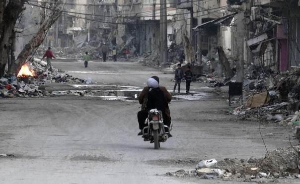 A man and a woman ride a motorcycle along a street filled with debris of damaged buildings in Deir al-Zor, Syria, March 5, 2014. Picture taken March 5, 2014. REUTERS/Stringer