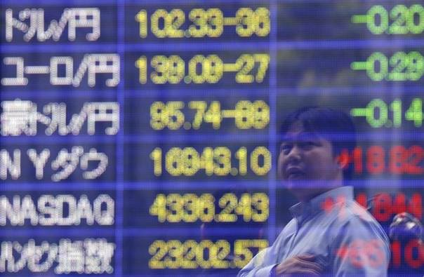 A man is reflected in an electronic board showing exchange rates outside a brokerage in Tokyo June 10, 2014. REUTERS/Issei Kato