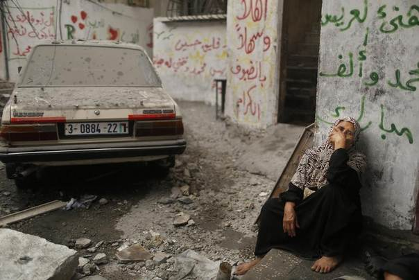 A Palestinian woman sits in a debris-strewn street as she looks at houses which witnesses said were damaged in an Israeli air strike that killed two children, in the northern Gaza Strip July 24, 2014.  REUTERS/Suhaib Salem