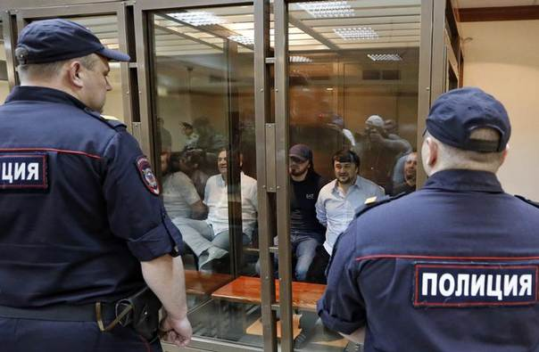 Defendants in the murder trial of Russian journalist and human rights activist Anna Politkovskaya, (L-R) Ibragim Makhmoudov, Lom-Ali Gaitukayev, Dzhabrail Makhmoudov, Rustam Makhmoudov and Sergei Khadzhikurbanov sit inside a glass-walled cage, while policemen stand guard in the foreground, during a court hearing in Moscow, June 9, 2014 REUTERS/Sergei Karpukhin