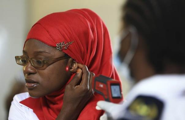 A female immigration officer uses an infrared digital laser thermometer to take the temperature of a female passenger at the Nnamdi Azikiwe International Airport in Abuja August 11, 2014. REUTERS/Afolabi Sotunde