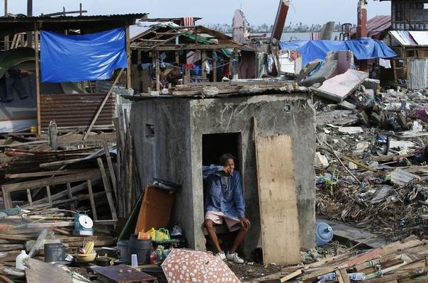 A typhoon survivor smokes a cigarette while resting by his partially-destroyed house, in Tacloban city, central Philippines, December 17, 2013. REUTERS/Erik De Castro