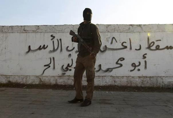 A Free Syrian Army fighter carries his weapon as he stands in front of graffiti that reads