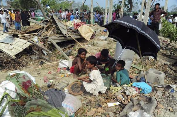 Children gather to retrieve their belongings from the wreckage after a tornado touched down in Brahmanbaria, March 23, 2013. A tornado swept through nearly two dozen villages southeast of the Bangladeshi capital, killing at least 20 people, officials said. REUTERS/Stringer