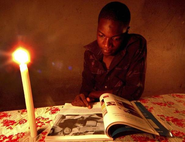 A student reads a book by candlelight in Zimbabwe's capital Harare May 2007. REUTERS/Philimon Bulawayo