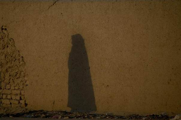 In this 2011 file photo the shadow of an Afghan woman wearing a burqa is seen on a mud wall as she walks down a street in Quetta, Pakistan. REUTERS/Naseer Ahmed