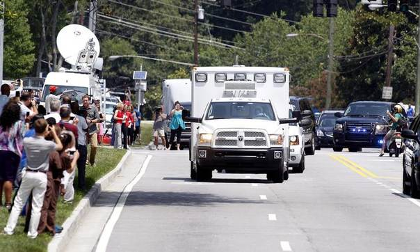 An ambulance carrying American missionary Nancy Writebol, 59, who is infected with Ebola in West Africa arrives past crowds of people taking pictures at Emory University Hospital in Atlanta, Georgia August 5, 2014. REUTERS/Tami Chappell