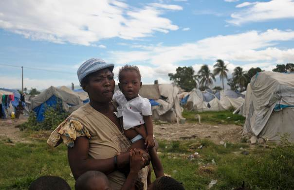 A Haitian woman surrounded by children stands in front of a tent camp for people uprooted by the 2010 earthquake, outside Port-au-Prince August 24, 2012.  REUTERS/Swoan Parker