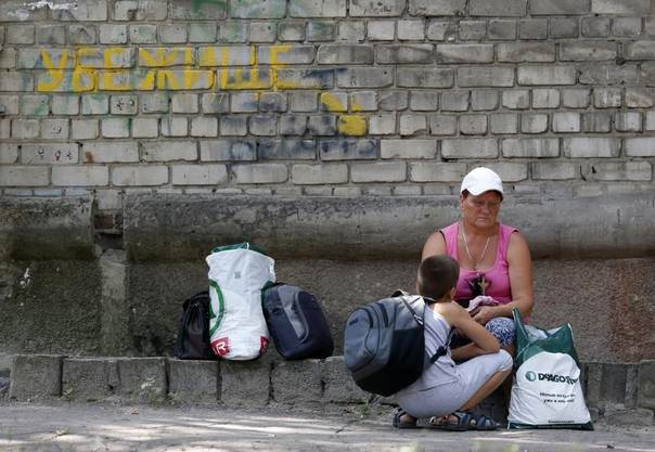 Local residents sit with their belongings near a bomb shelter in Donetsk, Ukraine, August 9, 2014. REUTERS/Sergei Karpukhin