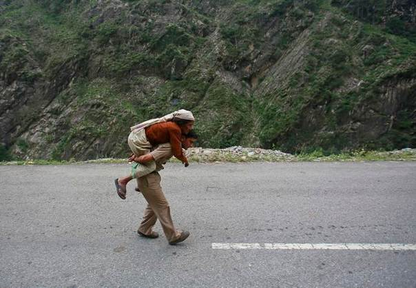 A policeman carries an old woman on his back during rescue operations in Govindghat in the Himalayan state of Uttarakhand after flash floods and landslides. Photo June 23, 2013. REUTERS/Danish Siddiqui