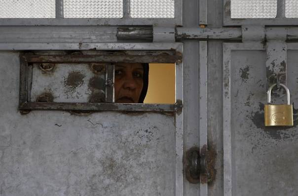 An Afghan woman looks out from a viewing panel in a door at Herat prison, western Afghanistan, December 9, 2013. REUTERS/Omar Sobhani