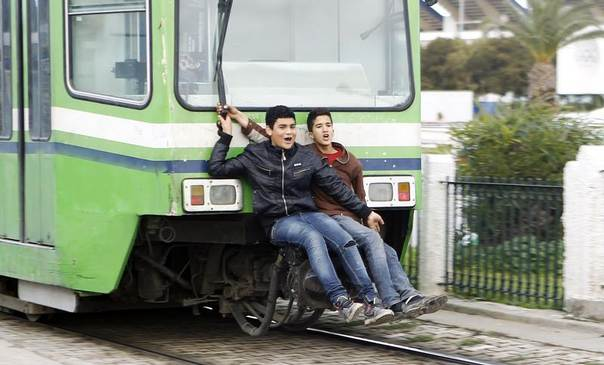 Boys ride on the back of a tram in Tunis, Tunisia, February 5, 2013. REUTERS/Zoubeir Souissi