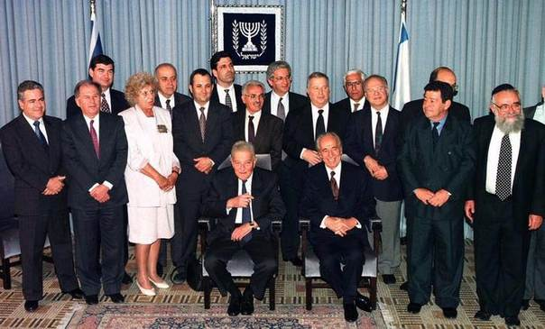 Newly sworn-in Prime Minister Shimon Peres sits with President Ezer Weizman (L) as he poses with his cabinet for a government family portrait November 22 in the president's residence after the government was ratified in the Knesset (Parliament), Ms.Shulamit in white, November 22, 1995 REUTERS/Jim Hollander