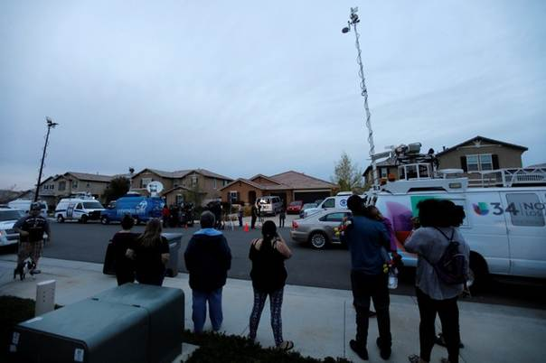 Neighbors stand and watch news crews outside the home of David Allen
