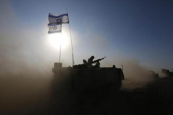 An Israeli soldier rides an armoured personnel carrier (APC) towards a staging area near the border with the Gaza Strip August 4, 2014.  REUTERS/Baz Ratner