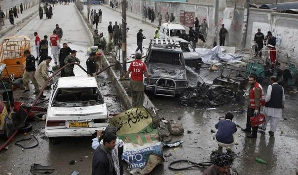 Firefighters extinguish a fire on burning vehicles, as security officials and rescue workers collect evidence at the site of a bomb attack in Quetta, Pakistan, March 14, 2014. REUTERS/Naseer Ahmed