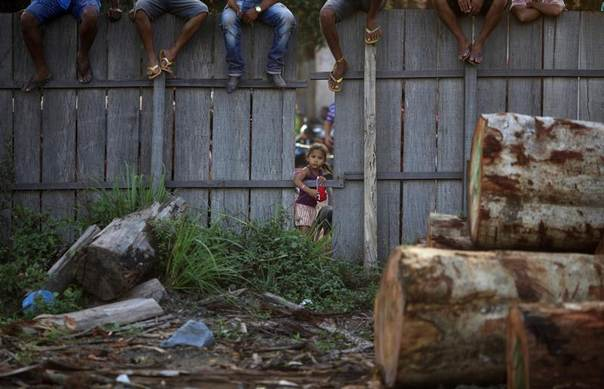 Town residents observe from a fence surrounding a sawmill, as Brazilian Army soldiers occupy the property during a raid on sawmills, haulers and loggers in Nova Esperanca do Piria, Para state, Sept. 25, 2013. REUTERS/Ricardo Moraes