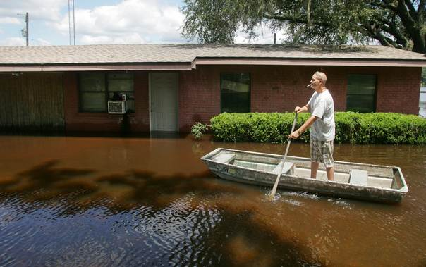 Troy Revis paddles to his flooded home on County Road 137 in Wellborn, Florida, on June 27, 2012. REUTERS/Phil Sears