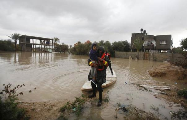 A member of the Palestinian civil defense carries a boy after evacuating him following heavy rains on a stormy day in Rafah, in the southern Gaza Strip, December 12, 2013. REUTERS/Ibraheem Abu Mustafa