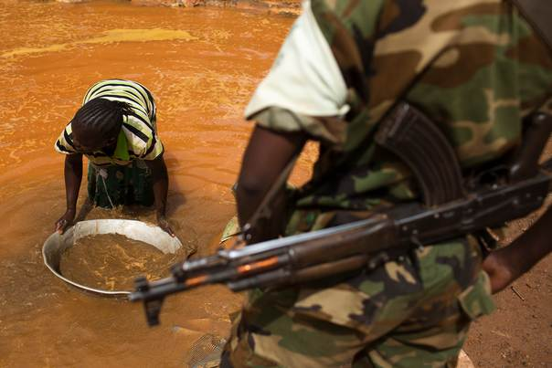 A former Seleka soldier looks at a woman panning for gold near Djoubissi, Central African Republic, on May 9, 2014. REUTERS/Siegfried Modola