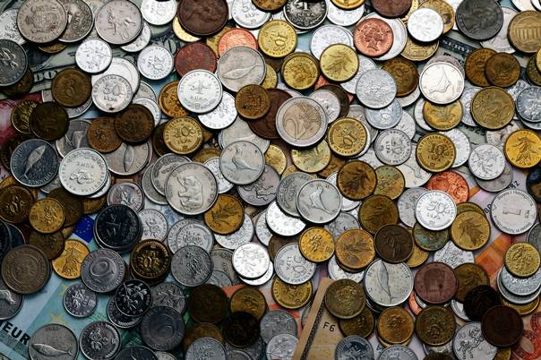 A picture illustration of coins from various countries laying on euro and kuna banknotes, taken on January 18, 2011. REUTERS/Nikola Solic
