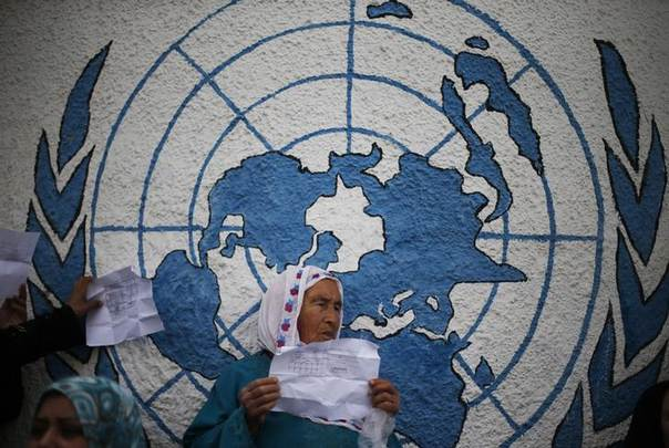 A Palestinian woman holds her refugee ration card during a protest demanding the United Nations Relief and Works Agency (UNRWA) to resume aid for refugees, in front of UNRWA headquarters in Gaza City April 8, 2013. REUTERS/Suhaib Salem
