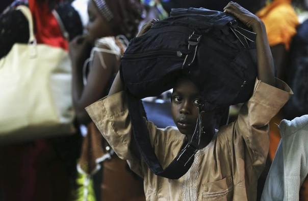 A boy, fleeing escalating violence in the Central African Republic, carries his bag at the Nnamdi Azikiwe International Airport in Abuja, January 3, 2014. REUTERS/Afolabi Sotunde