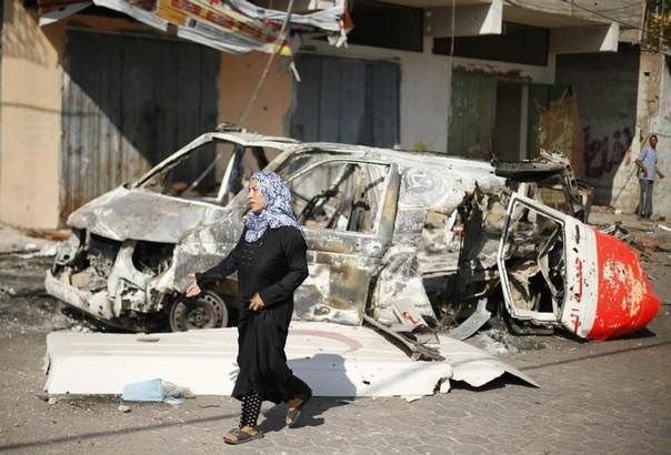 A Palestinian woman walks past the wreckage of an ambulance in Beit Hanoun town, which witnesses said was heavily hit by Israeli shelling and air strikes during Israeli offensive, in the northern Gaza Strip August 1, 2014. REUTERS/Suhaib Salem